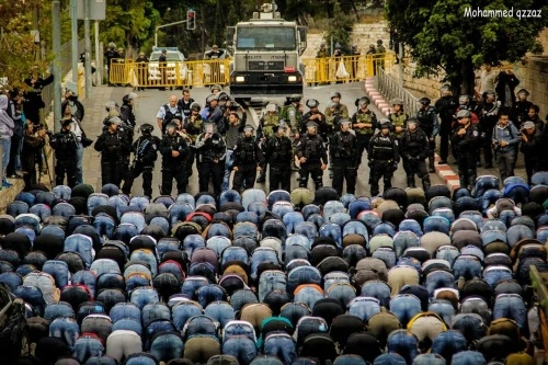Palestinians pray in front of Israeli right police